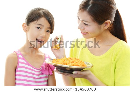 Girl eating food with mom - stock photo