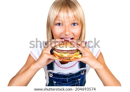 Girl eating Hamburger. Child with hamburger. Pretty little girl eating a sandwich isolated on white background  - stock photo