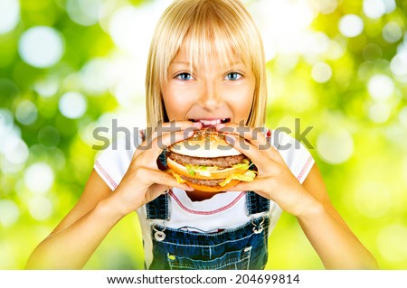 Girl eating Hamburger. Child with hamburger. Pretty little girl eating a sandwich over nature green bokeh background  - stock photo