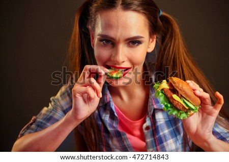 Girl eating hamburger. Girl biting slice of cucumber from hamburger.