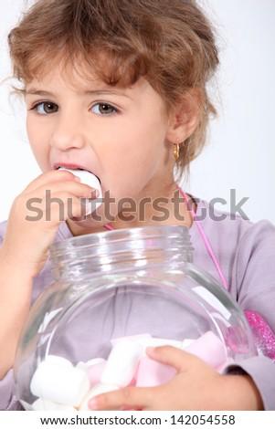 Girl eating marshmallows - stock photo