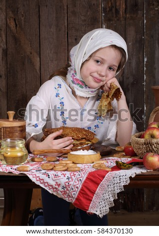 Girl eating pancakes with sour cream during the carnival