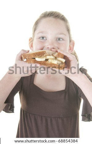 Girl eating peanut butter and banana sandwich