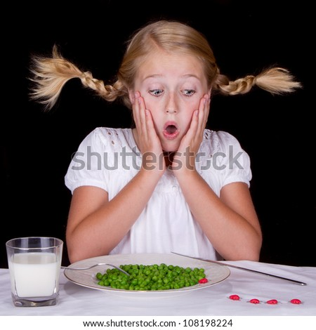 girl eating peas with bugs on the table isolated on black - stock photo
