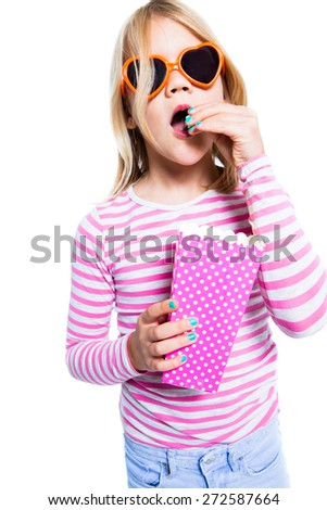 Girl eating pop corn out of a pink container wearing heart shape sunglasses - stock photo