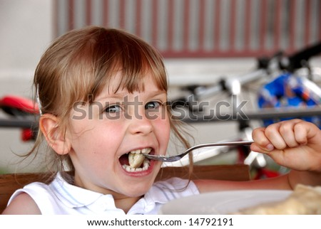 Girl eating ravioli in restaurant - stock photo
