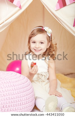 girl eating strawberries while sitting in a tent with balloons decoration - stock photo