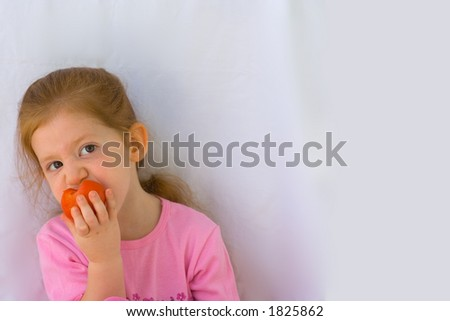Girl eating tomato - stock photo
