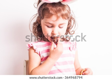 Girl eats a chocolate little eggs after Easter hunting