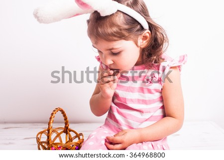 Girl eats a chocolate little eggs after Easter hunting - stock photo