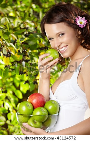 Girl eats an apple with bowl of apples in a summer garden - stock photo