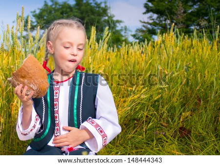 girl eats bread on the field with wheat in Ukrainian costume