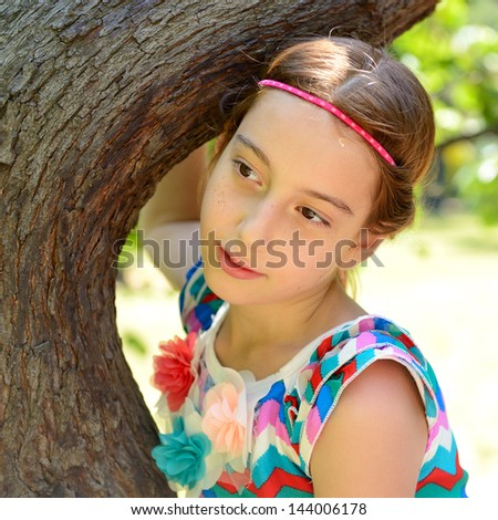 girl embrace tree, smiling and looking at camera - stock photo