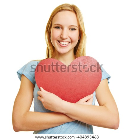 Girl embracing a big red heart as love symbol with her arms
