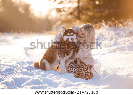 Girl embracing cute dog in winter park. The girl with the siberian husky - stock photo
