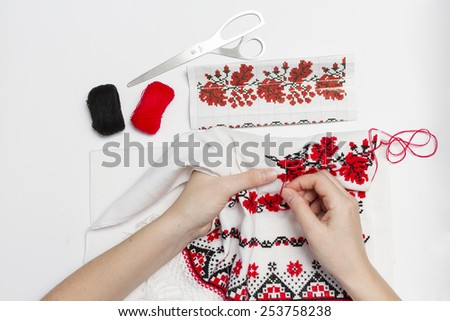 Girl embroider pattern red thread on a towel. - stock photo