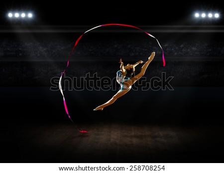 Girl engaged art gymnastics at sports hall - stock photo
