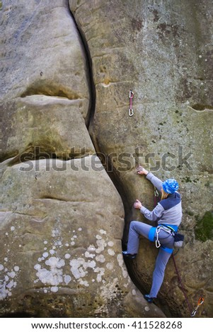 Girl engaged in rock climbing on the cliffs.