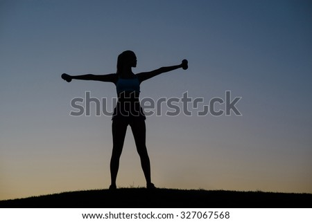 Girl engaged in sports on the nature. Silhouette of the figure of the athlete. Girl shakes her muscles on the sunset background. Morning fitness on the nature. - stock photo