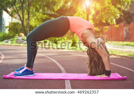 Girl engaged in yoga, gymnastics, fitness outdoors