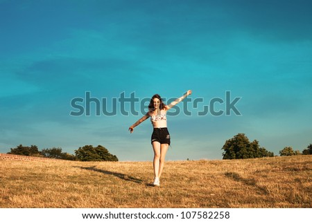 girl enjoy in summer day run on the hill sky in background - stock photo