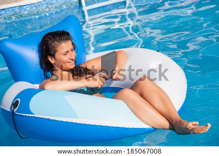 girl enjoying e-book  in the pool on vacation