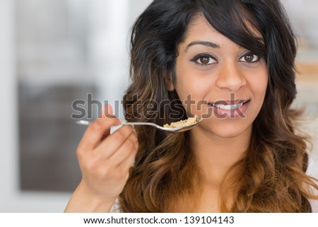 Girl enjoying eating cereal and holding up spoon