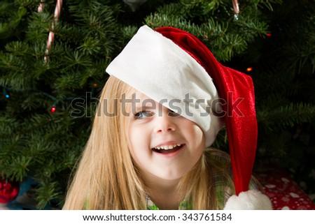 Girl enjoying her christmas presents and christmas hat - stock photo