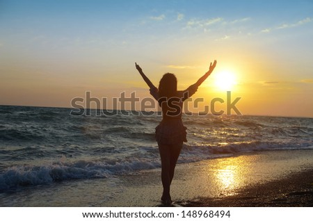 girl enjoying the sea air and the beautiful sunset on the beach - stock photo