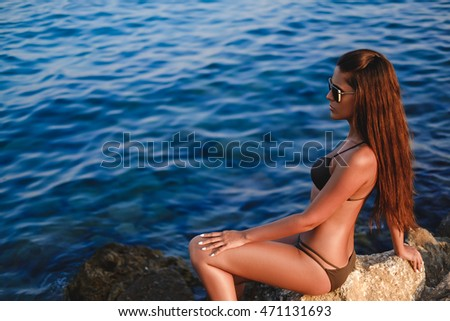 Girl enjoying the sun on the rock by the sea. Summertime