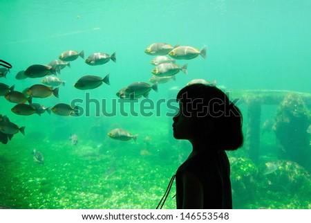 Girl enjoying the underwater life at aquarium - stock photo