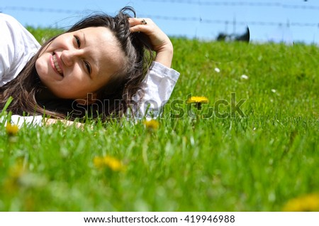 Girl enjoys lying in the green grass
