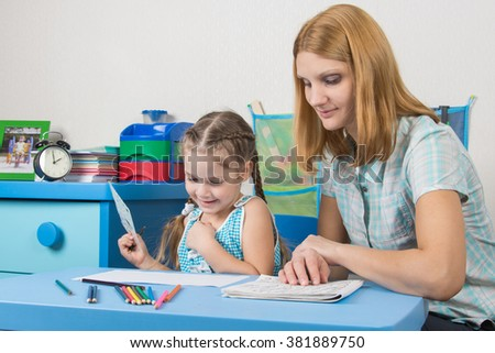 Girl enjoys painting with teacher in kindergarten - stock photo