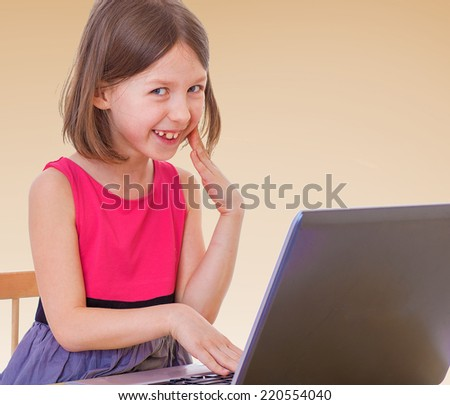 girl enjoys playing on the computer.The concept of development of the child, the child's upbringing. - stock photo