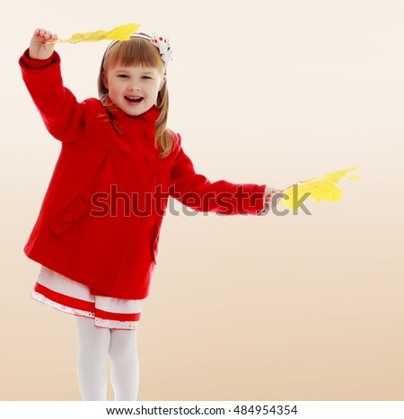Girl enjoys the autumn weather. On a brown background. Joyful little girl in a bright red coat waving yellow maple leaves.