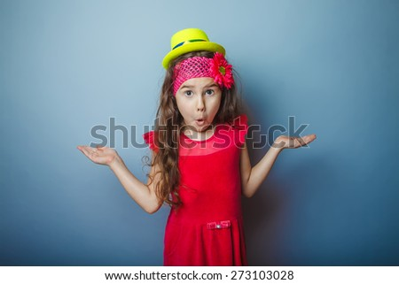 Girl European appearance haired child of seven years in a bright dress in yellow hat surprised on a gray background, spread her hands - stock photo