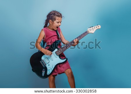 Girl European appearance ten years  playing guitar sings on  a blue  background - stock photo