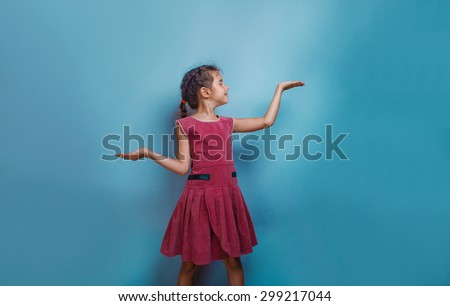 Girl European appearance ten years shows gesture scales hands on a blue background - stock photo