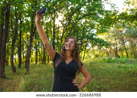 Girl European appearance young brown-haired woman in a black dress makes self on the phone in the forest, laughter, joy