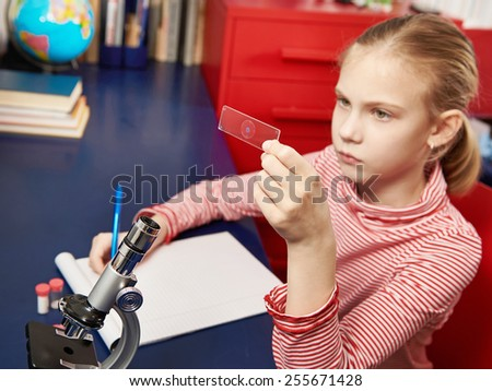 Girl examines drug for the microscope for learning home table - stock photo