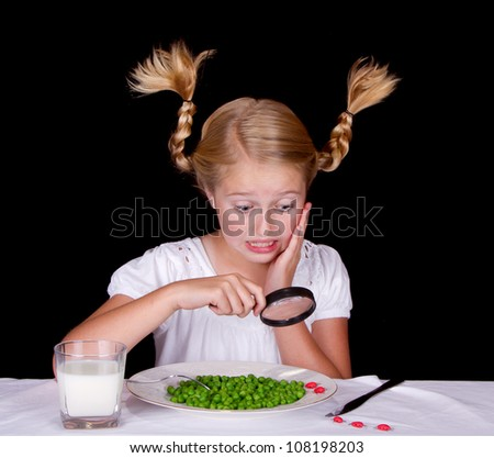 Girl examining bugs on table with magnifying glass, isolated on black