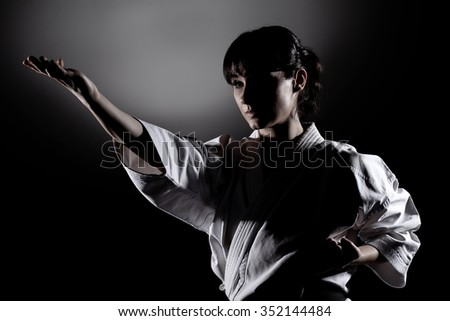 girl exercising karate, against black background - stock photo