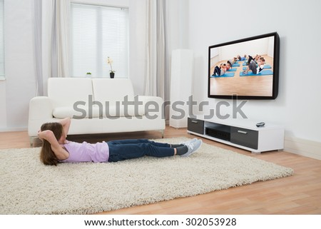 Girl Exercising On Carpet While Watching Television In Living Room - stock photo