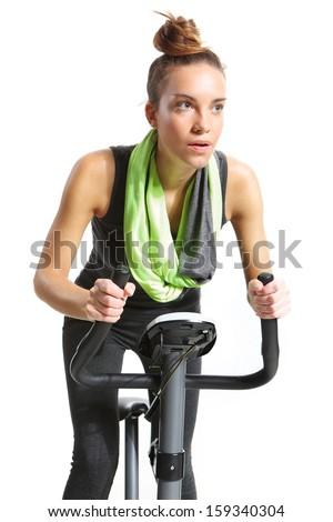 Girl exercising on exercise bike - stock photo