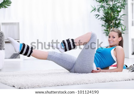 Girl exercising with ankle weights for strengthening legs