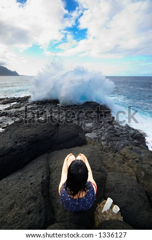 Girl facing huge wave on Kauai Hawaii. More with keyword Series001C. - stock photo