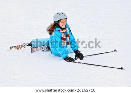 Girl falling on skis in the powder snow - stock photo