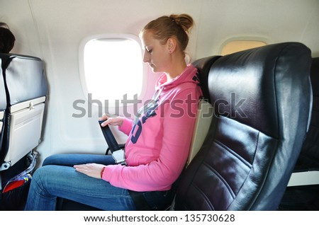 Girl fastening her seat belt - stock photo
