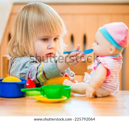 girl feeding a doll at home in the children's room - stock photo