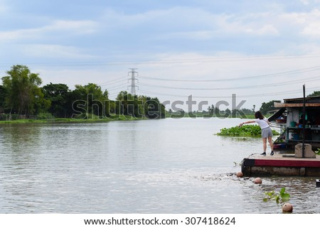 girl feeding fish in river(background)